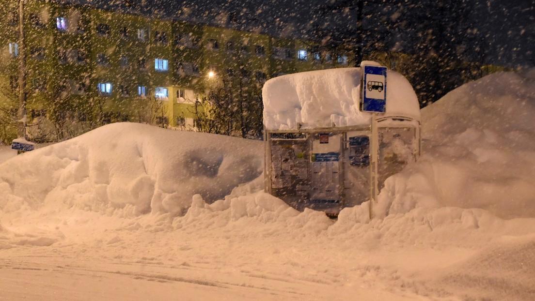 Coches, señales de tráfico y paradas de autobús quedan enterrados bajo enormes montones de nieve en una ciudad rusa
