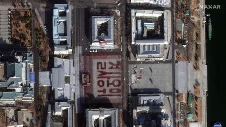 """FOTO: Miles de norcoreanos creancon sus cuerpos la frase """"defender con su vida"""" durante el ensayo de un desfile"""