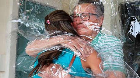 """En el momento más oscuro de la pandemia en Brasil, una """"cortina de abrazo"""" permite a los ancianos volver a tocar a sus seres queridos (VIDEO)"""