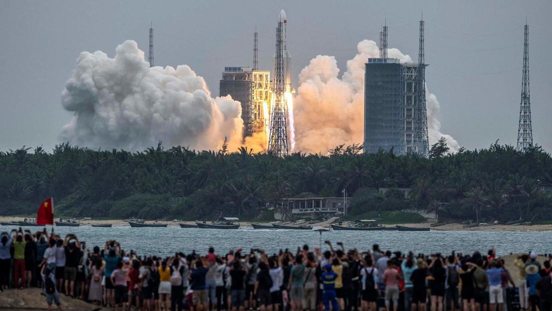 Decenas de personas observan desde una playa cómo el cohete Long March-5B Y2 despega del centro de lanzamiento espacial de Wenchang, en Hainan, China. 29 de abril de 2021.