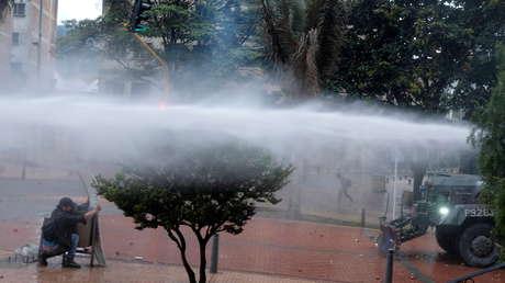 VIDEOS: Un chorro de agua disparado por agentes del Esmad desde una tanqueta durante protestas en Colombia derriba a un joven, que termina en la UCI
