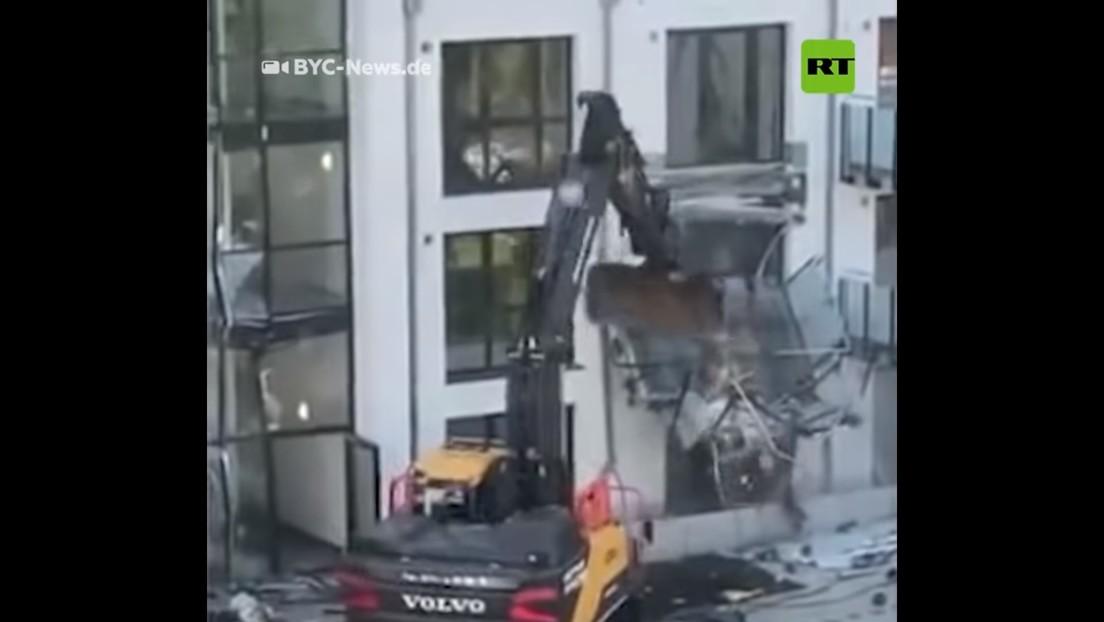 Un contratista se venga de la falta de pagos destruyendo la fachada de un edificio residencial con una retroexcavadora (VIDEO)