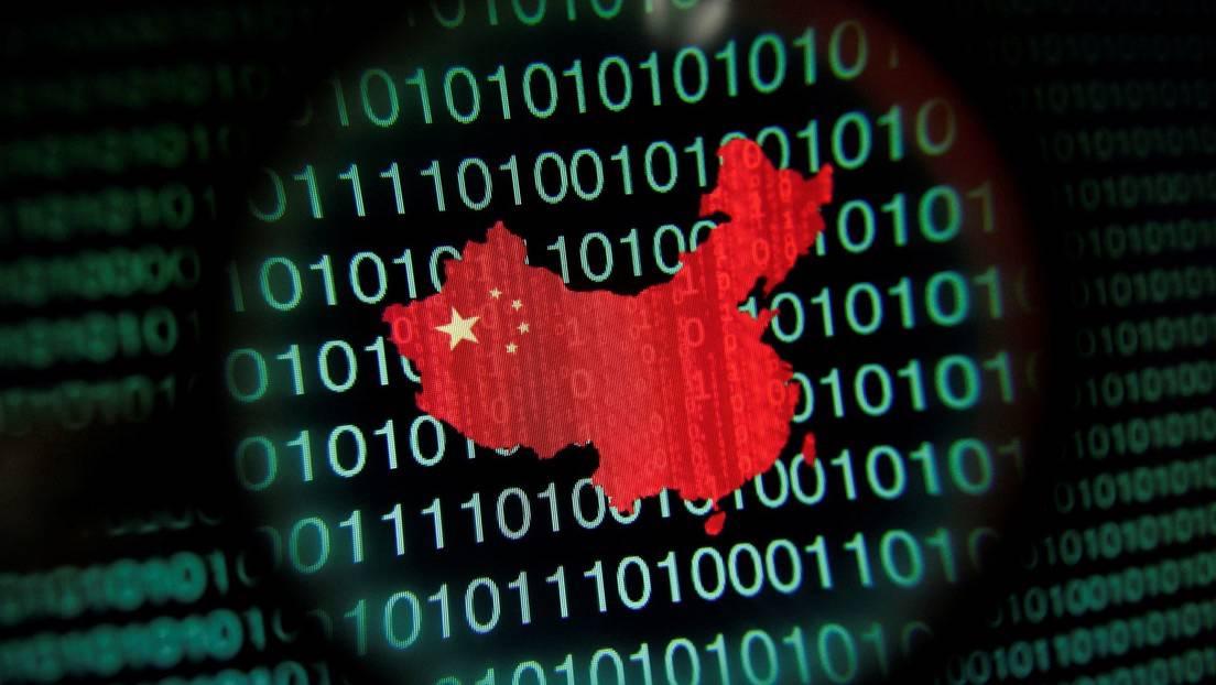 Mapa de China visto a través de una lupa en la pantalla de una computadora que muestra dígitos binarios.