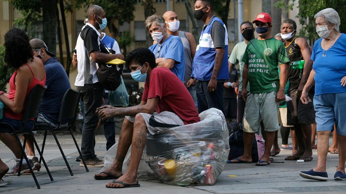 """""""Suplican por unos pocos huesos para cocinar"""": Las desoladoras imágenes de brasileños que buscan comida entre los desechos de animales"""