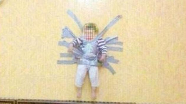 Una imagen muestra a un niño saudita pegado a la pared con cinta adhesiva