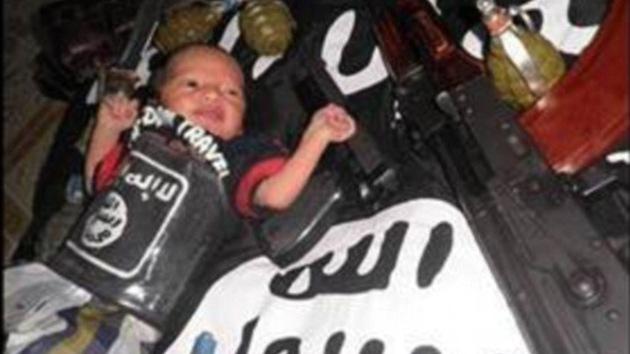 'Bebé de la yihad' posa con un Kaláshnikov sobre la bandera del Estado Islámico