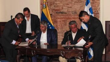 Tsipras und González (sitzend) bei der Unterzeichnung der zur Zusammenarbeit in der Energiepolitik - Quelle: MRE.GOV.VE