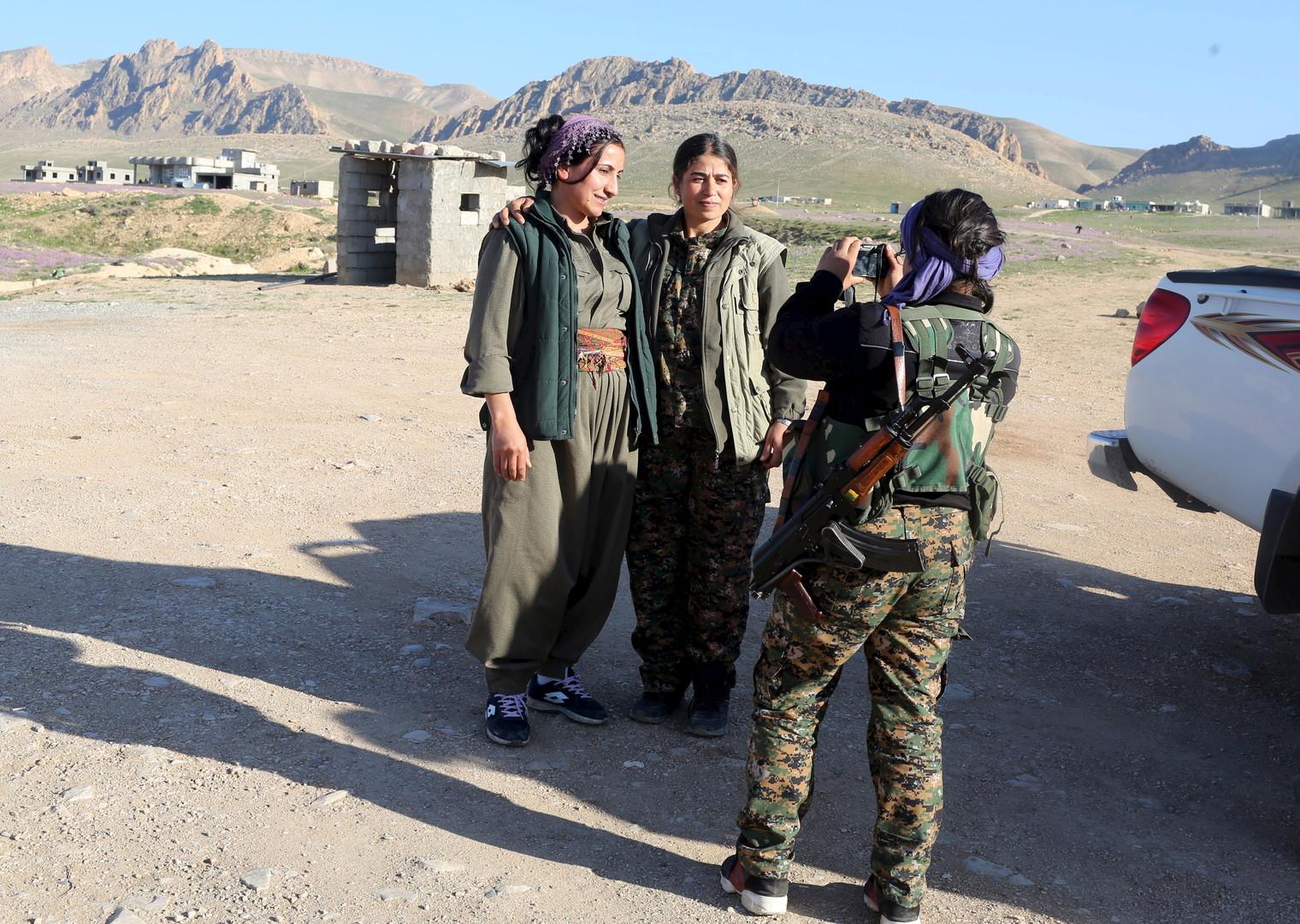 Kämpferinnen machen ein Selfie, als Frauen einer anderen Einheit sie besuchen. Die Rauchsäulen der Gefechte sind von der Basis aus zu sehen.