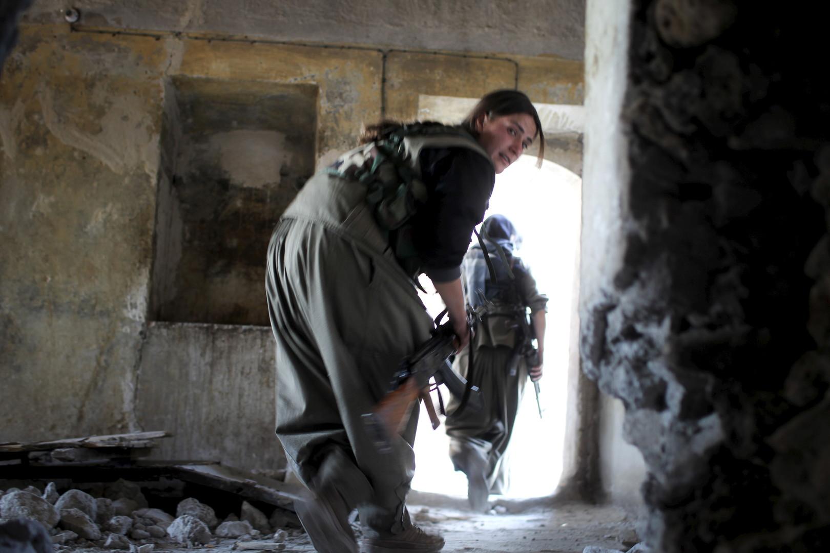 Kämpferinnen auf dem Weg an die Front in einem zerschossenen Gebäude.