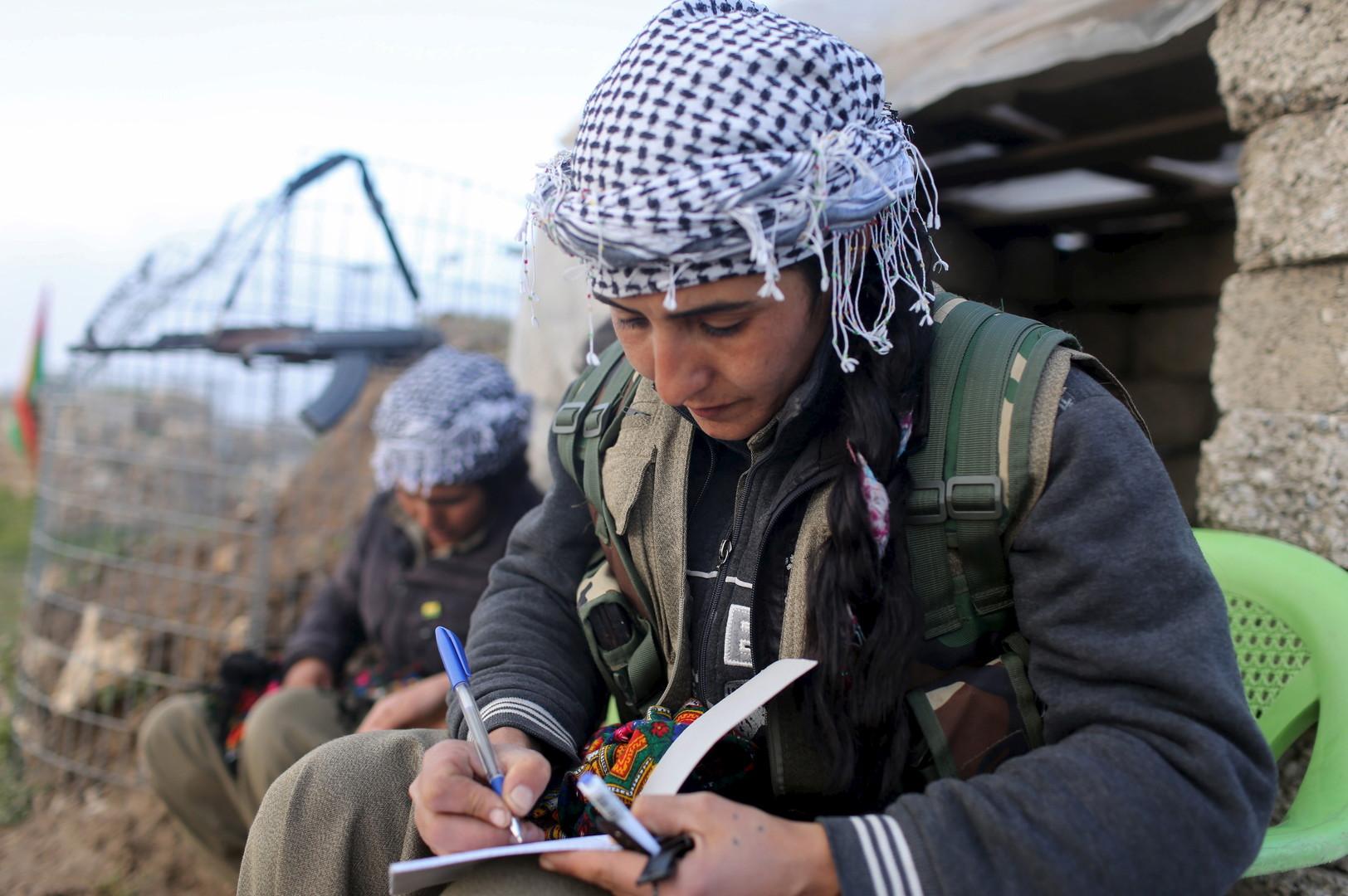 Eine Kämpferin schreibt Notizen in ein Buch, während sie ihre Wache an der Basis in Sinjar verbringt, März 2015.
