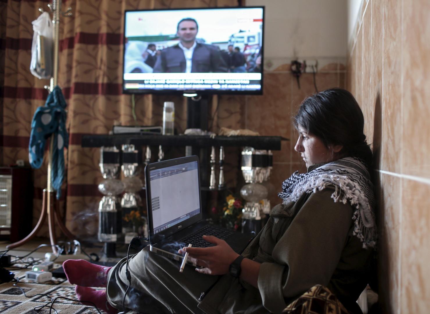 Eine Kämpferin der PKK arbeitet an ihrem Laptop. Im Hintergrund läuft ein kurdischer Fernsehkanal.
