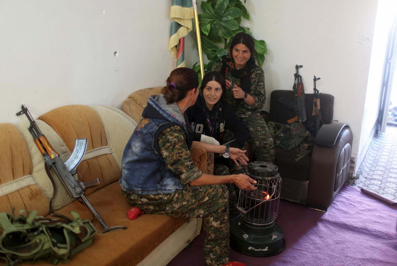 Eine PKK-Kämpferin sitzt mit anderen Frauen zusammen, darunter eine Kämpferin der YBS (rechts).