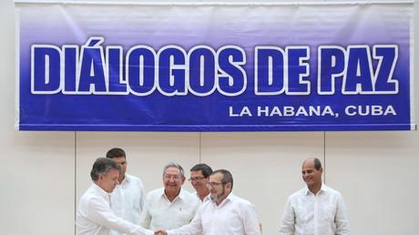 Der kubanische Präsident Raúl Castro freut sich am Handschlag zwischen dem kolumbianischen Präsidenten Juan Manuel Santos (L) und dem Anführer der FARC-Rebellen, Rodrigo Londono, besser bekannt unter seinem nom de guerre Timochenko.