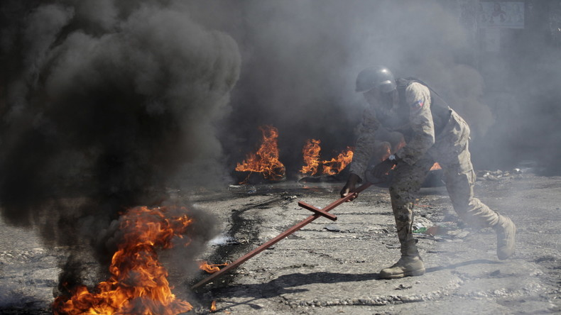 Ein Polizist auf Haiti versucht eine brennende Barrikade abzuräumen in Port-au-Prince, Haiti, 19. Januar 2016.