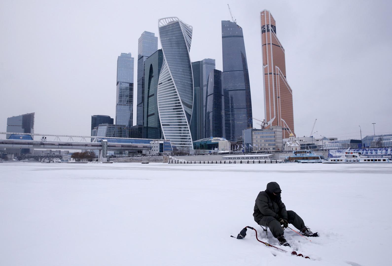 Ein Mann angelt am schneebedeckten Moskwa-Fluss in der Nähe des Moskauer Business-Distrikts