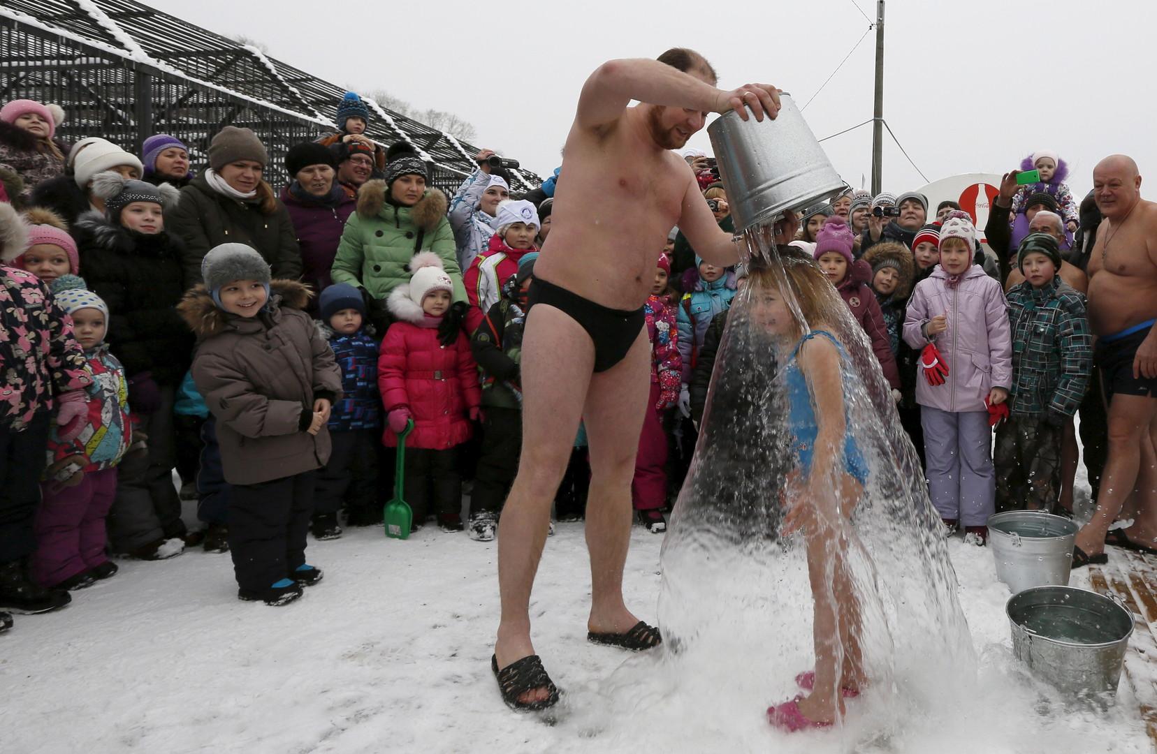 Grigory Browerman, Mitglied im Winterschwimm-Club in der sibirischen Stadt Krasnoyarsk, überschüttet seine 6-jährige Tochter mit einem Eimer kaltem Wasser