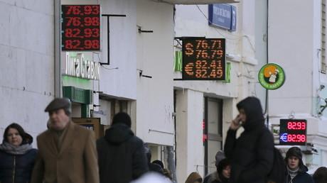 Passanten vor Tafeln mit aktuellen Wechselkursen für den Euro und den US-Dollar in Moscau am 14. Januar 2016.