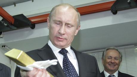 Wladimir Putin hält beim Besuch der Zentralbank im Moskau einen Goldbarren, Januar 2011.