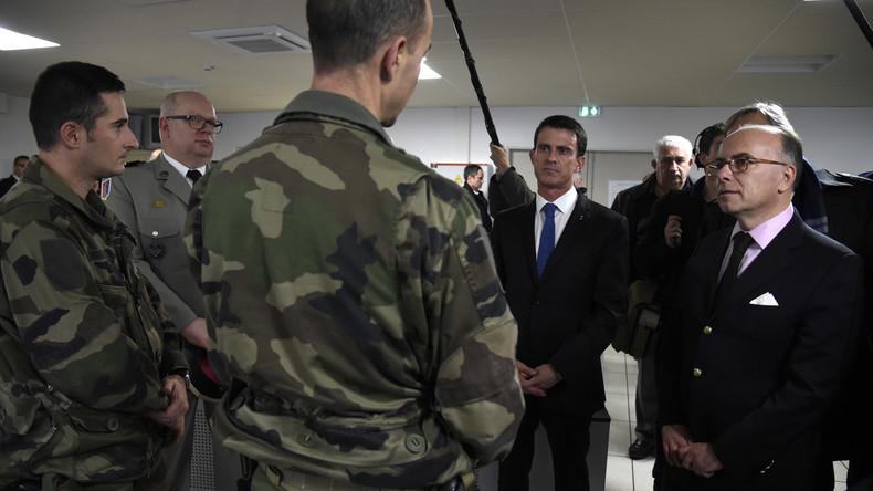 Frankreichs Premier Manuel Valls (2. v.r) und Innenminister Bernard Cazeneuve (r.) sprechen mit Armeeoffizieren bei der Einweihung einer Polizeistation in Evry.