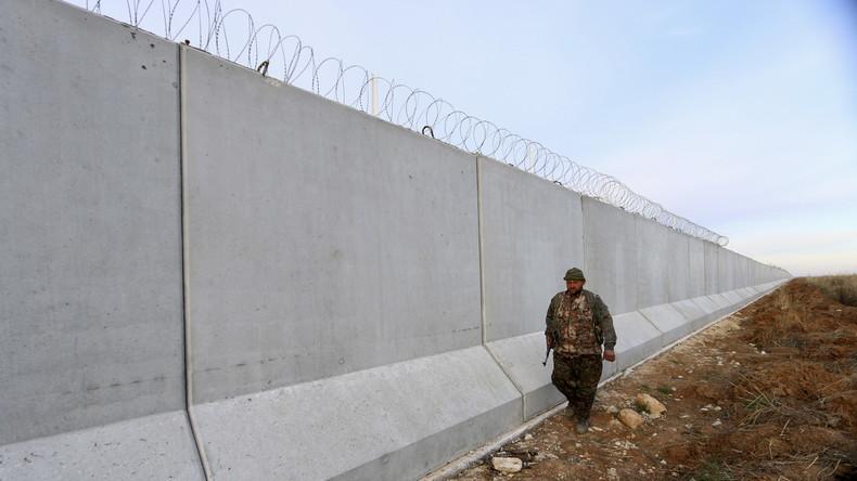 Ein Kämpfer der syrisch-kurdischen Selbstverteidigungskräfte (YPG) läuft Patrouille an einer Mauer, die nach kurdischer Darstellung vom türkischen Militär auf syrischem Gebiet errichtet wurde, 29. Januar 2016