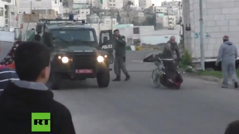 Israelische Grenzpolizisten werfen behinderten Palästinenser mit seinem Rollstuhl um