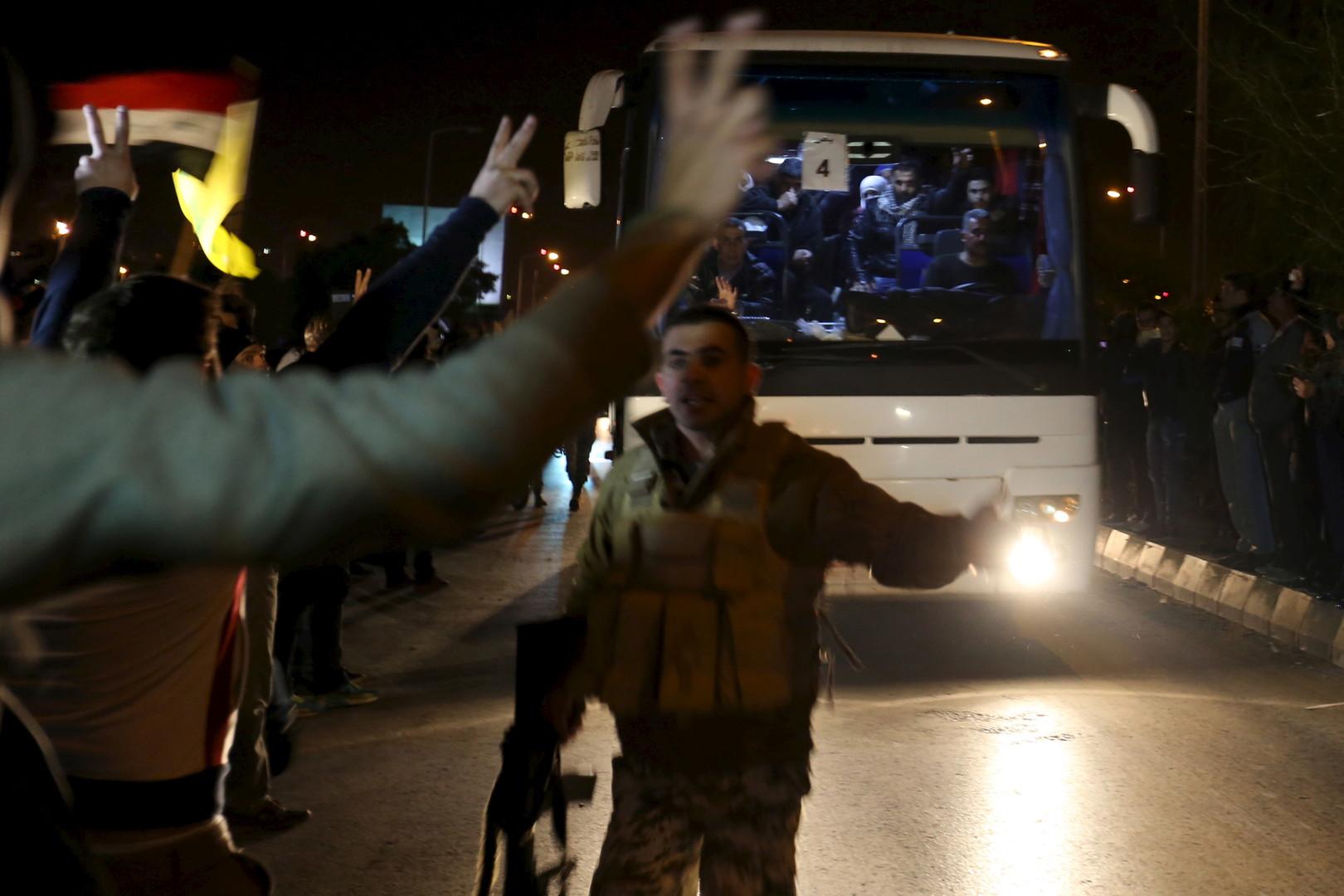 Die syrische Bevölkerung begrüßt Busse, die die Menschen aus den von aufständischen Milizen belagerten Städten Al-Foua und Kefraya bringen, Dezember 2015.