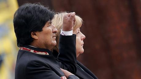 Morales und Merkel befinden sich beide in ihrer dritten Amtszeit und streben eine vierte an. Doch während es bei Merkel als Zeichen demokratischer Kontinuität gilt, ist es bei Morales laut Opposition und USA Zeichen von Despotismus, den es zu verhindern gilt.