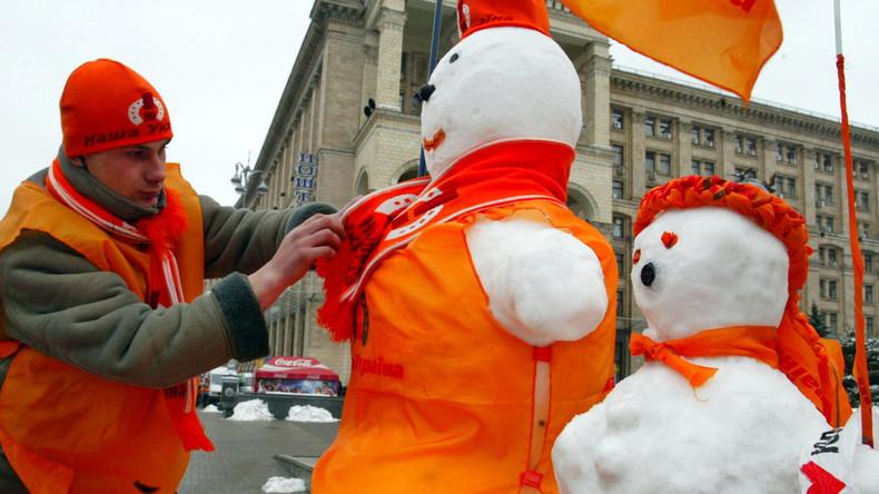 """Wie die Farbrevolution zum Schmelzen bringen? Ein Mann dekoriert Schneemänner auf dem Unabhängigkeitplatz in Kiew in den Farben der """"Orangen-Revolution"""""""