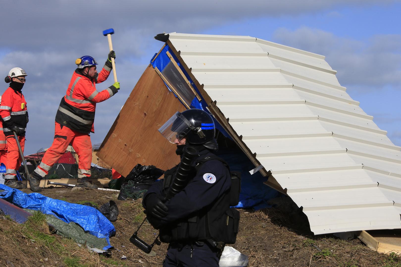 Arbeiter zerstören einen improvisierten Flüchtlingsunterstand