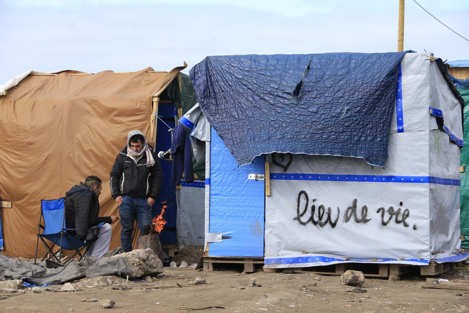 """Migranten in Calais neben einem Zelt mit der Aufschrift """"Ort des Lebens"""""""