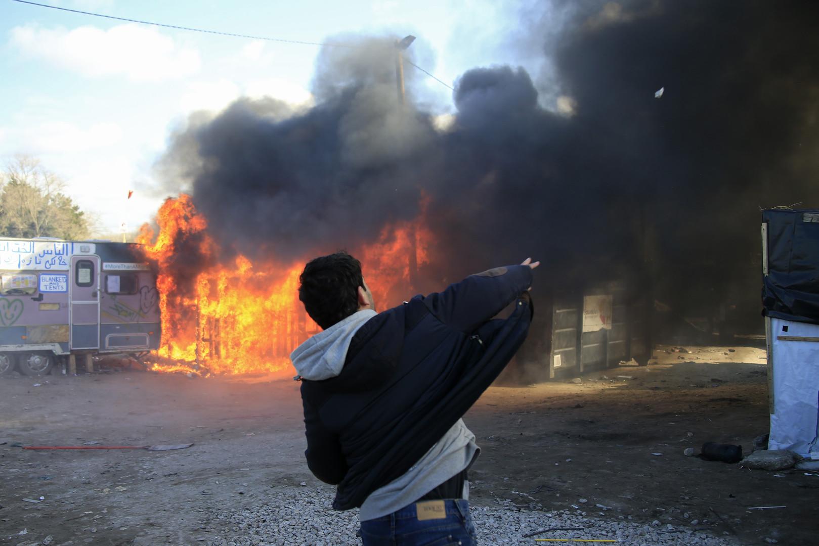 Ein Jugendlicher wirft Steine in die Flammen als Protest gegen die Räumungen