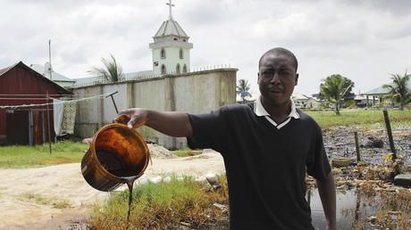 Ein Dorfbewohner zeigt einen Eimer voll mit Rohöl verschmutzem Wasser aus dem Niger-Delta, verursacht durch ein jahrelanges Leck in einer  Shell-Pipeline, Oktober 2015.