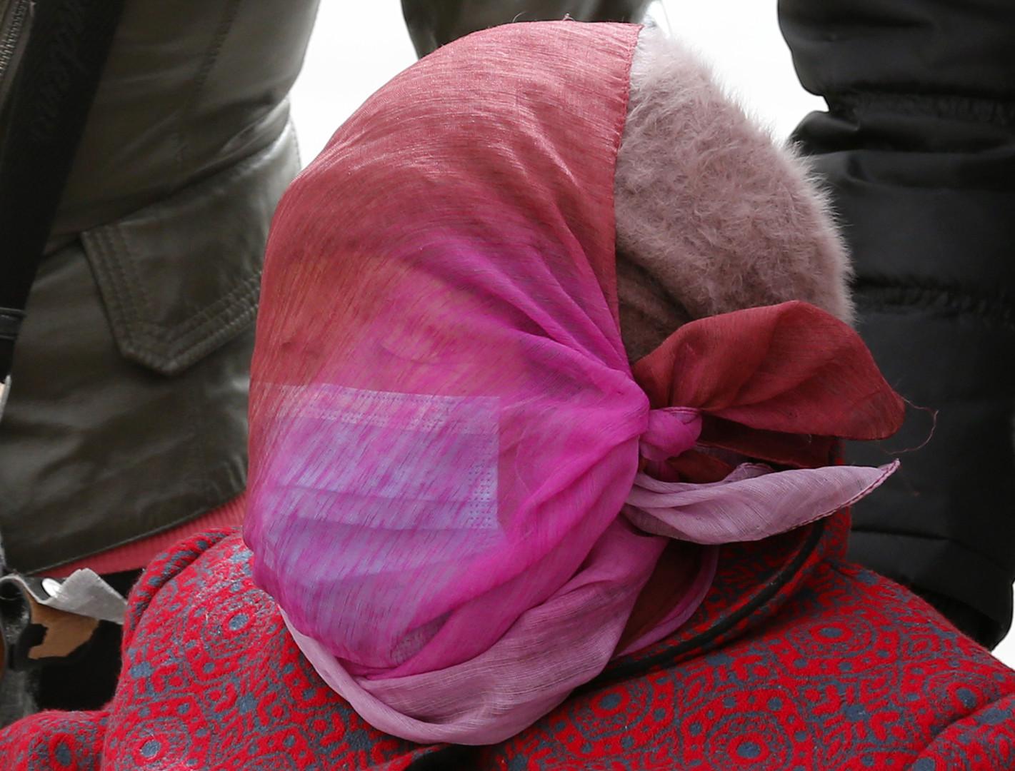 Frau, die sich das Gesciht mit einem Kopftuch bedeckt, Tiananmen-Platz, Peking, März 2013.