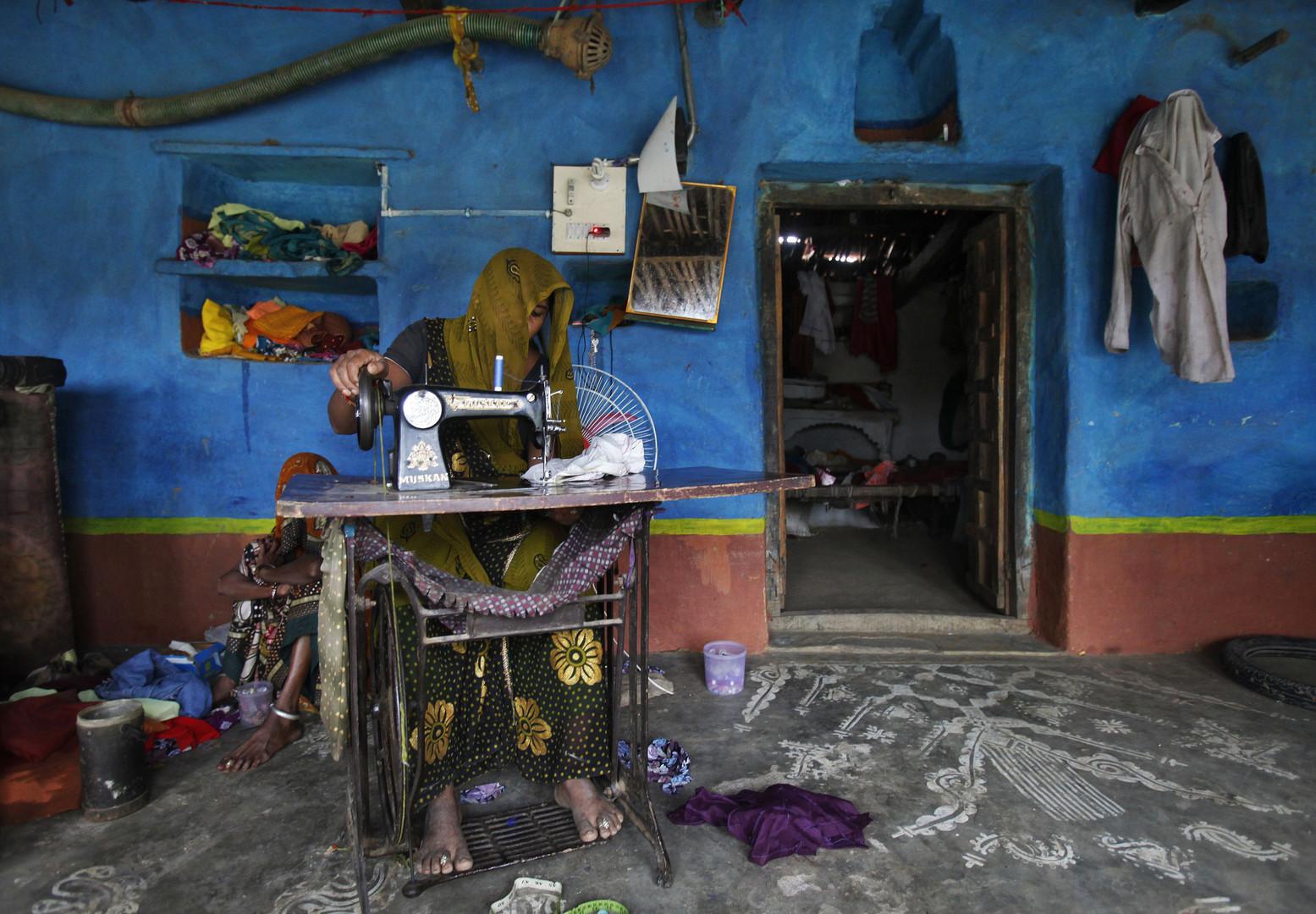 Näherin bei der Arbeit in Madhya Pradesh, Indien, Juni 2012.
