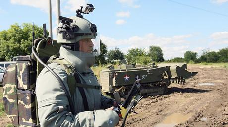 Pionier des Südlichen Militärischen Ingenieurkorps im Schutzanzug hält die Fernsteuerkonsole des Uran-6-Robotersystems.