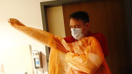 Ein Sanitäter legt seine Schutzkleidung an - Doch im Zusammenhang mit der Flüchtlingskrise scheinen die Sorgen übertrieben