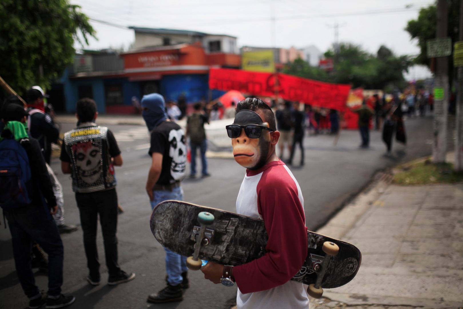 Ein Skateborder mit Maske am Rande der 1. Mai-Demonstration in San Salvador.