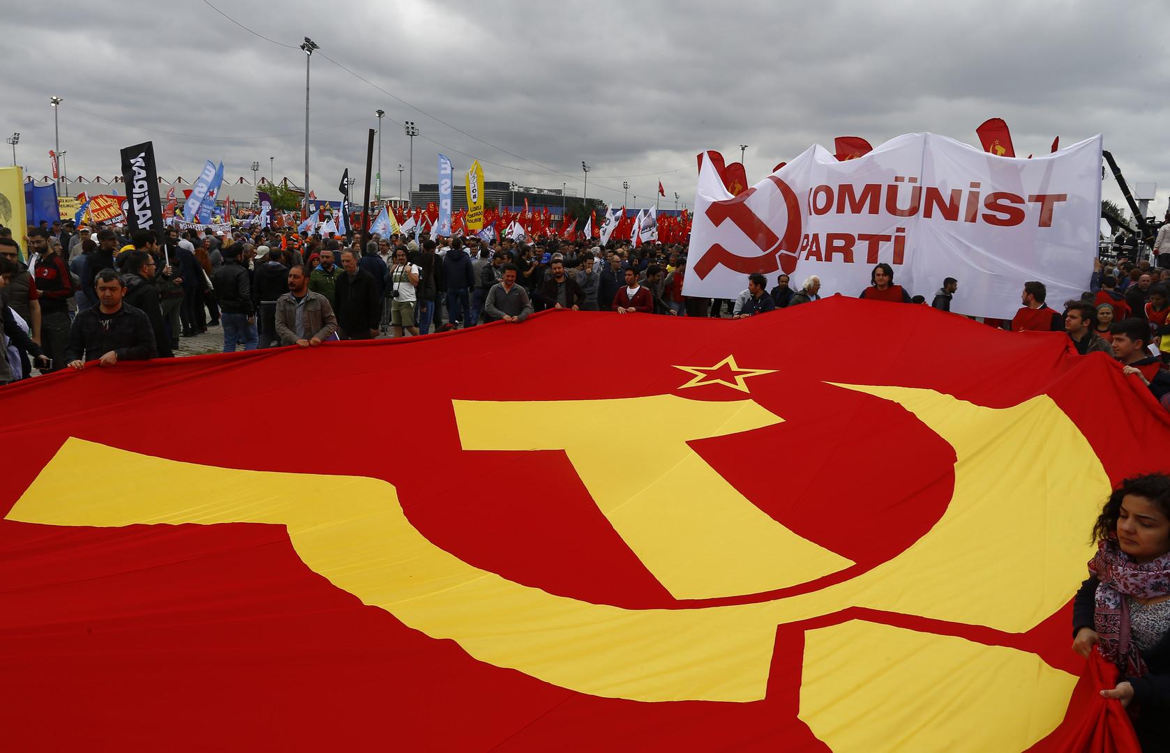 Mitglieder einer kommunistischen Partei hinter der Fahne mit Hammer und Sichel in Istanbul, Türkei. Bei den Auseinandersetzungen mit Sicherheitskräften wurde ein Mann von einem Wasserwerfer getötet.