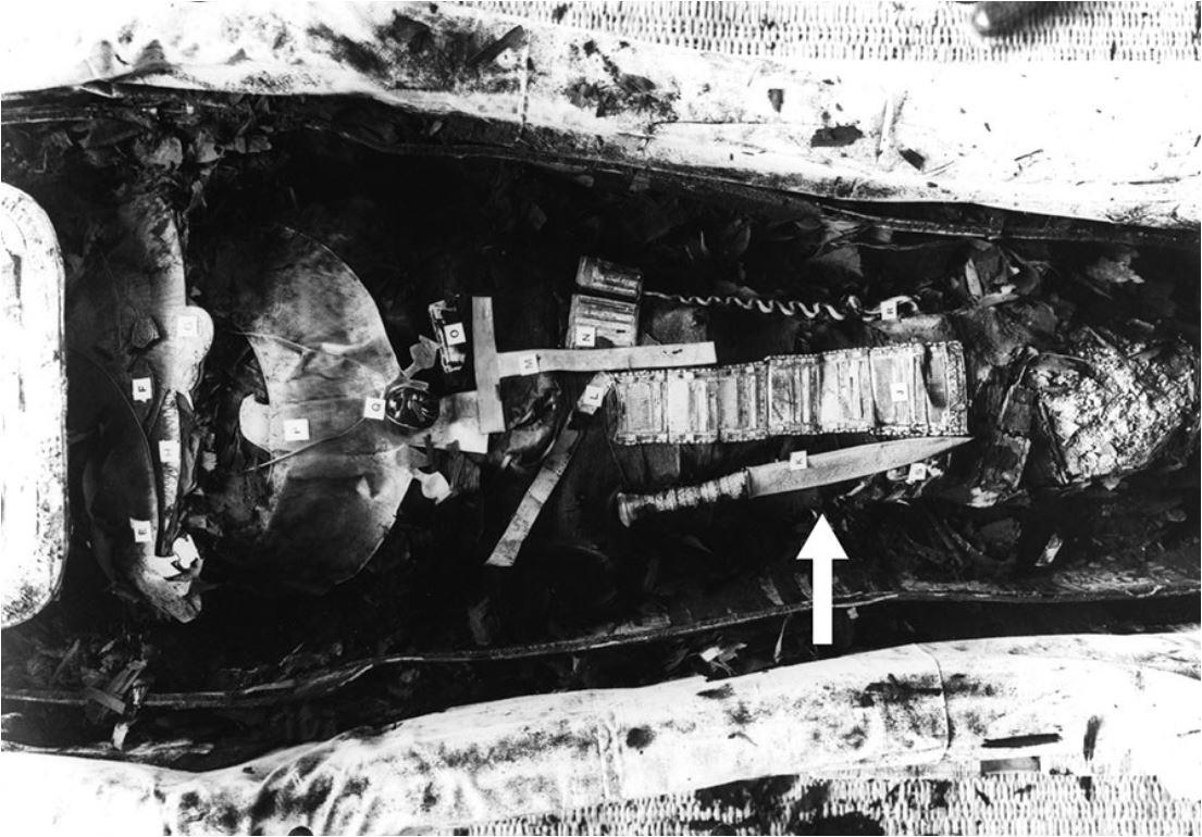 Die Mumie von König Tutanchamun. Ein schwarz-weiß Foto von Tutanchamuns Mumie zeigt den Eisernen Dolch (34,2 cm lang) auf dem rechten Oberschenkel liegend (Pfeil).