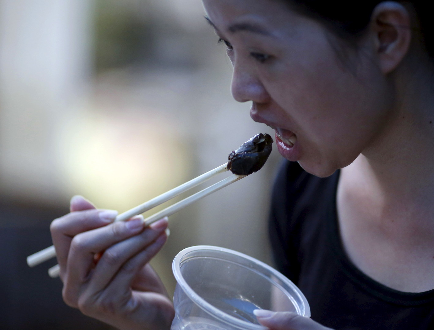 Eine Chinesin beim Hundeessen in Yulin: Jedes Jahr im Juni findet hier ein lokales Festival statt, bei dem Hundefleisch mit Litchi angeboten wird.