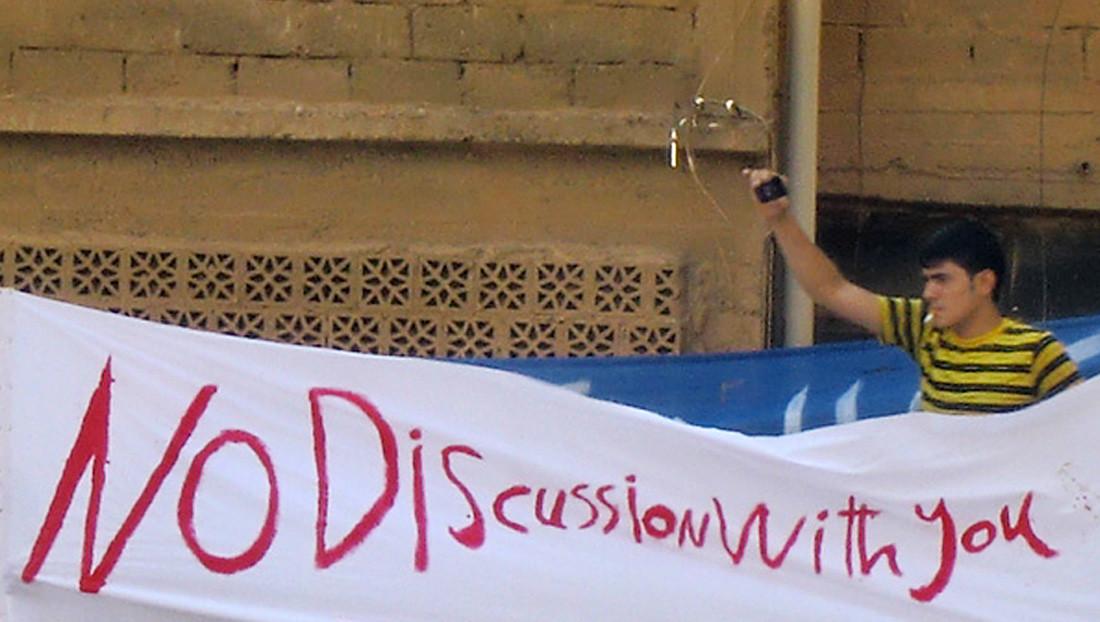 """Protestierender in Syrien hinter einem Transparent in Deir al-Zour, während die """"syrische Opposition"""" in Istanbul im Juli 2011 mit den westlichen Staaten verhandelt."""