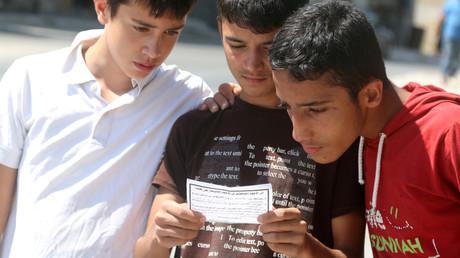 Jugendliche lesen Flugblätter der regulären Armee. Sie bitten die Bevölkerung mit der Armee zusammenzuarbeiten und fordern die Aufständischen auf, ihre Waffen niederzulegen, Aleppo, 28. Juli 2016.