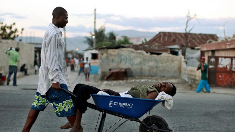 Haitianer, der Symptome von Cholera zeigt, wird in den Slums von Cite-Soleil in Port-au-Prince, in einer Schubkarre transportiert, Haiti, 19. November 2010