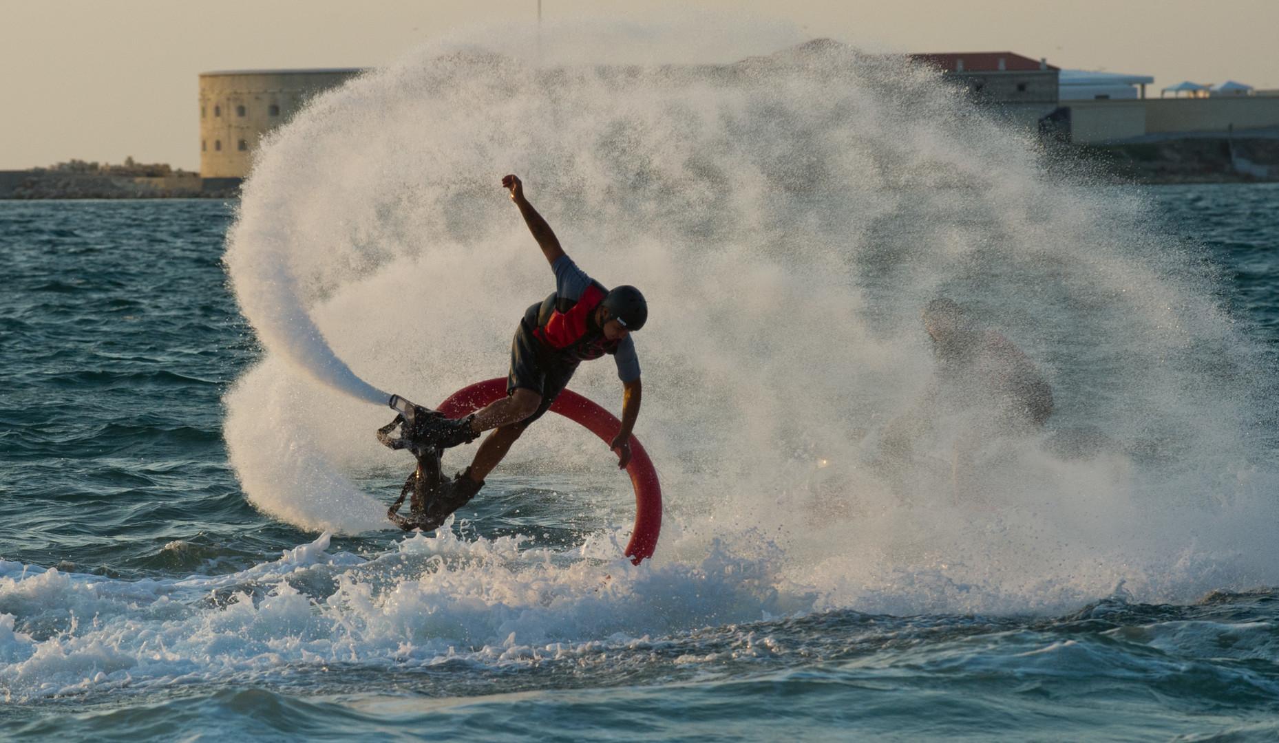 Der Flyboarder taucht ins Wasser, wenn der Wasserdruck im Schlauch abnimmt, und sobald er sich erhöht, steigt der Sportler wieder in die Luft.