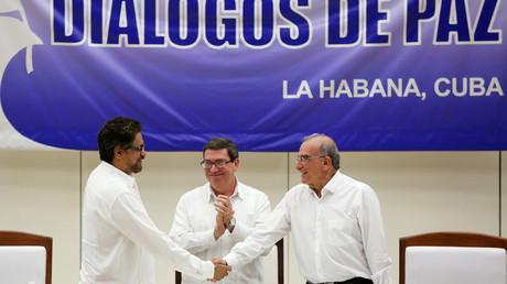 Der Chef-Unterhändler der FARC Ivan Marquez (links) und der Vertreter der kolumbianischen Regierung Humberto de la Calle (rechts) reichen sich die Hände, während Kubas Außenminister Bruno Rodriguez zuschaut. Der sozialistische Inselstaat spielte eine bedeutende Rolle als Vermittler.
