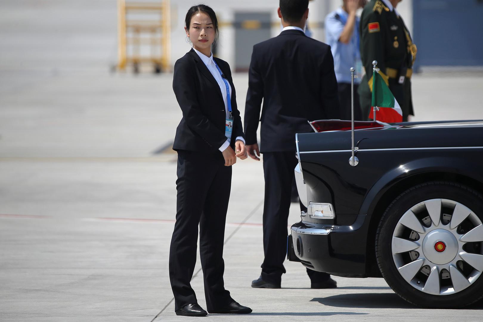 Sicherheitsfrau am Wagen für den italienischen Premierminister, Matteo Renzi, im Flughafen Hangzhou Xiaoshan