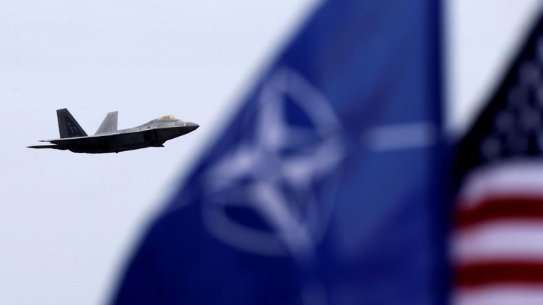 Ein amerikanischer Kampfjet des Typs F-22 Raptor vor einer NATO- und einer US-Flagge.