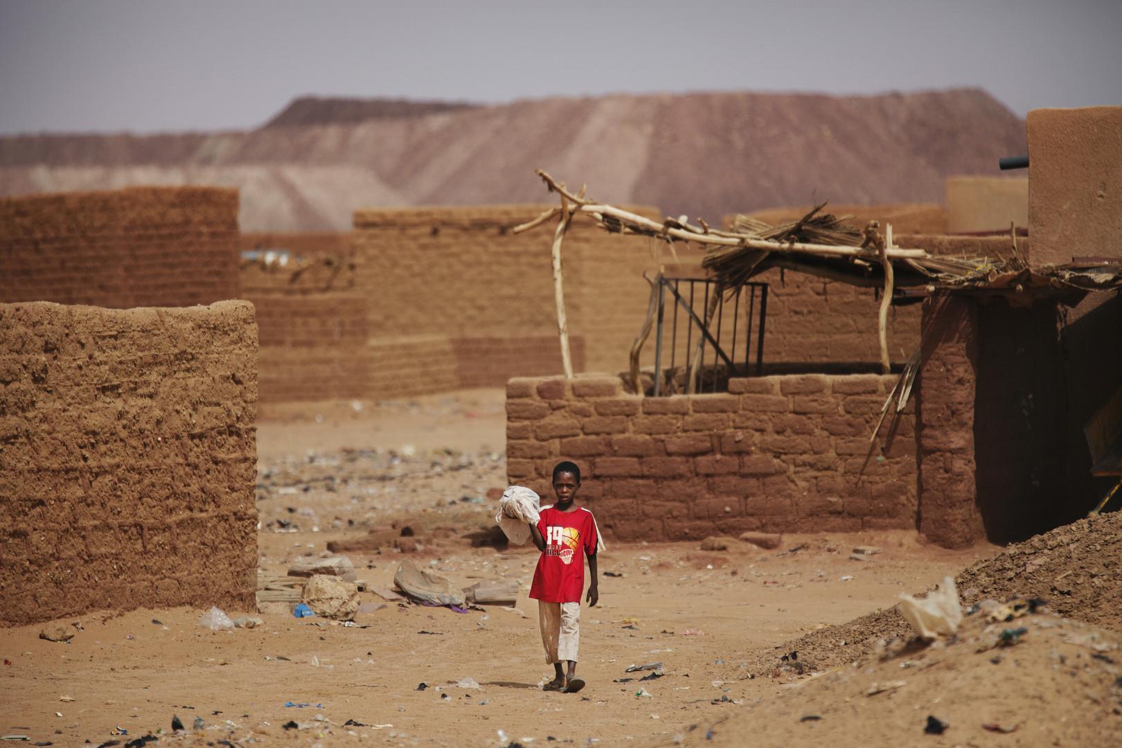 Erin Junge in einer Wohnsiedlung vor den Abraumhalden der Uran-Mine Areva Cominak in Arlit, September 2013.
