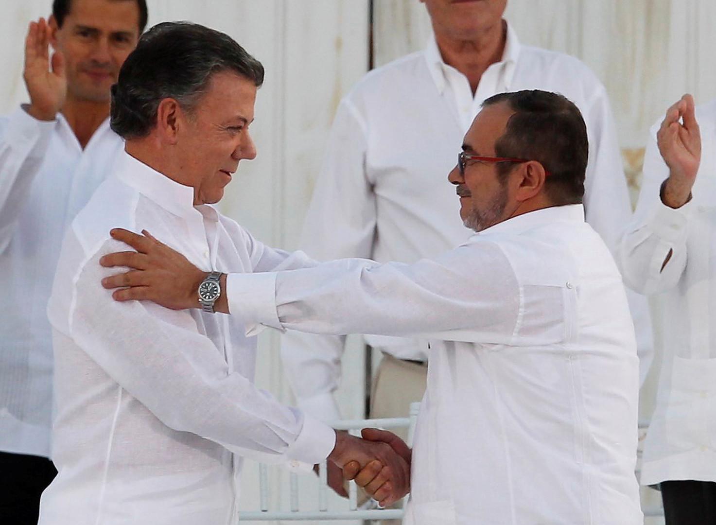 """Der kolumbianische Präsident Juan Manuel Santos (links) and FARC-Führer Timoleón Jiménez """"Timochenko"""" beim Handschlag zur Besiegelung des Friedensvertrages, Cartagena, Kolumbien, September 26, 2016."""