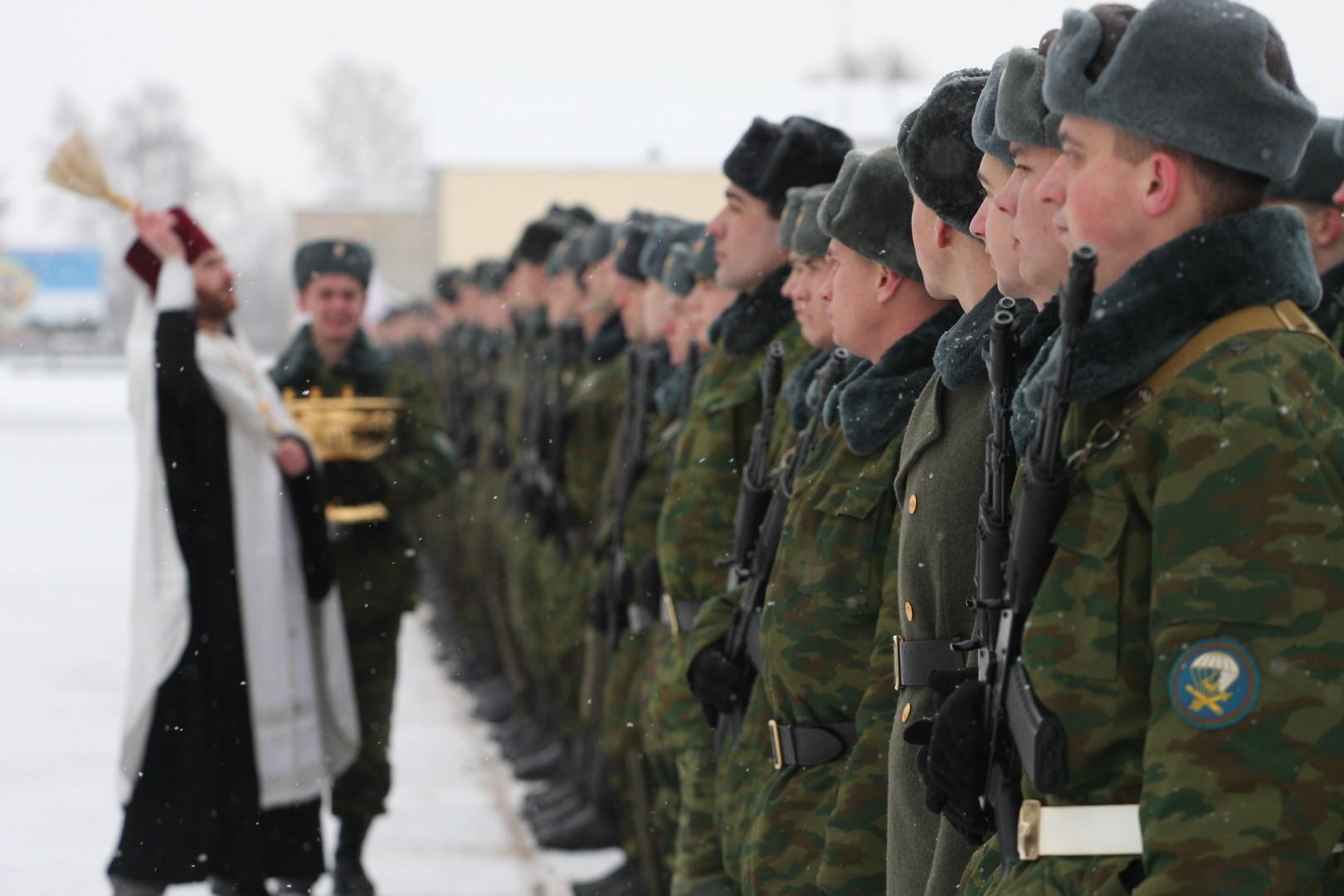 Ein Militärpfarrer bespritzt Rekruten mit Weihwasser während der Vereidigung.